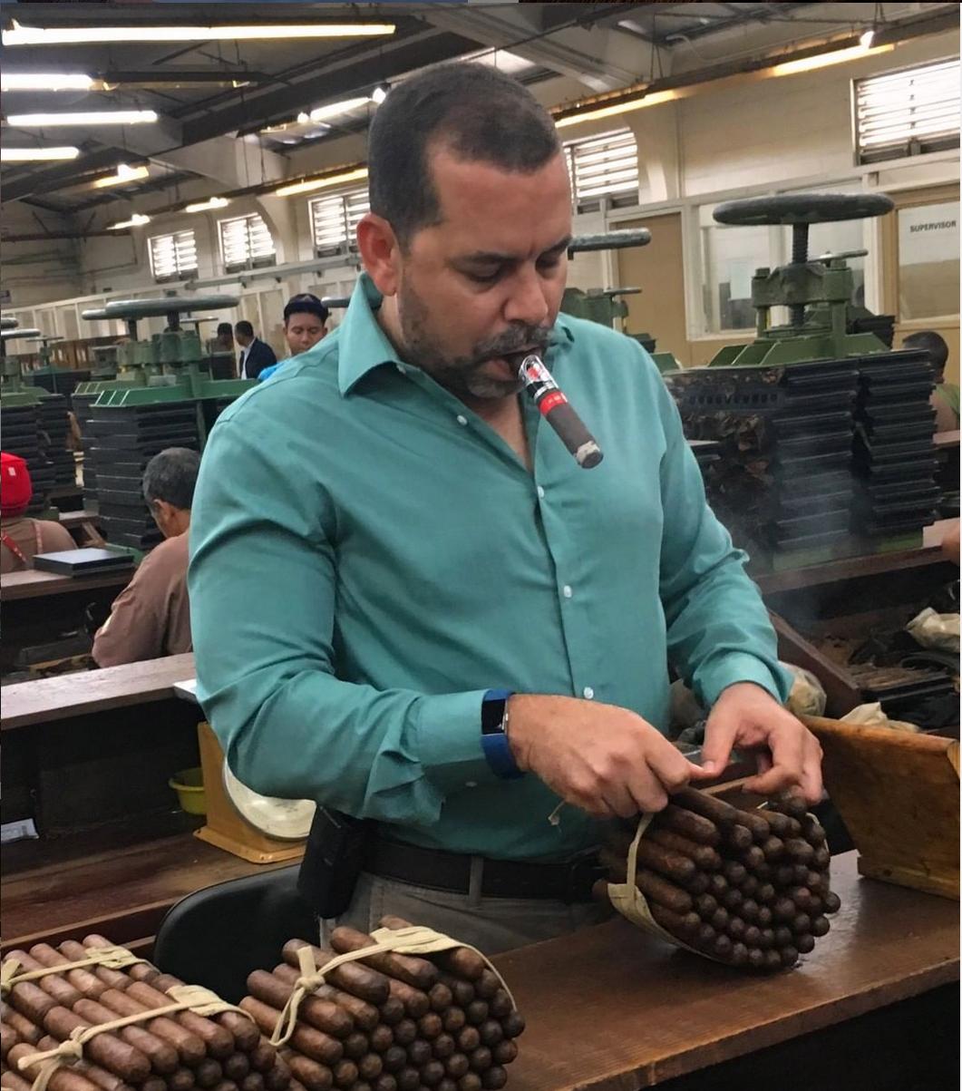 Yuri Guillen, Operations Manager of La Gloria Cubana Cigars Smokes a Cigar While Inspecting a Bundle