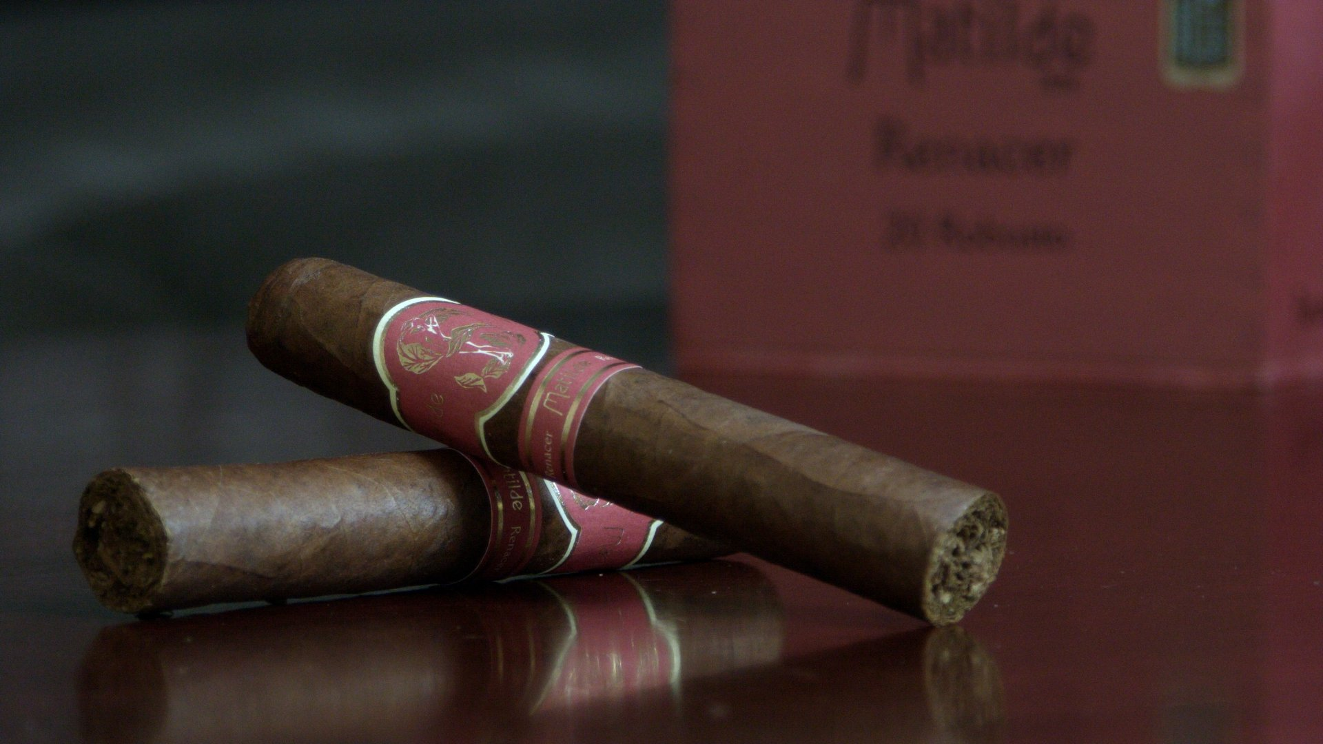 two matilde renacer robusto cigars on a table with the box as a backdrop