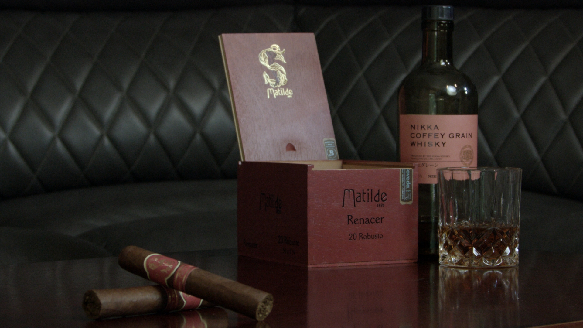 matilde robusto cigars shown on a table next to their open box and bottle and glass of nikka coffey grain whisky
