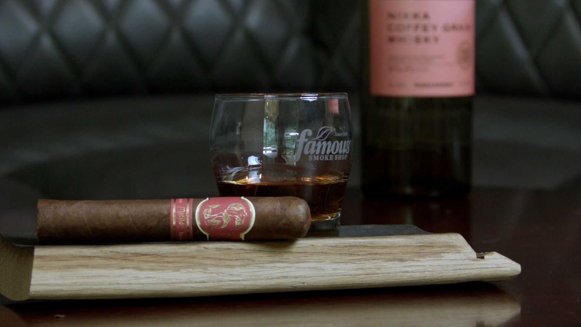 matilde renacer robusto cigar and famous smoke shop rocks glass on a wooden stave with a bottle of nikka coffee grain whisky cigar pairing