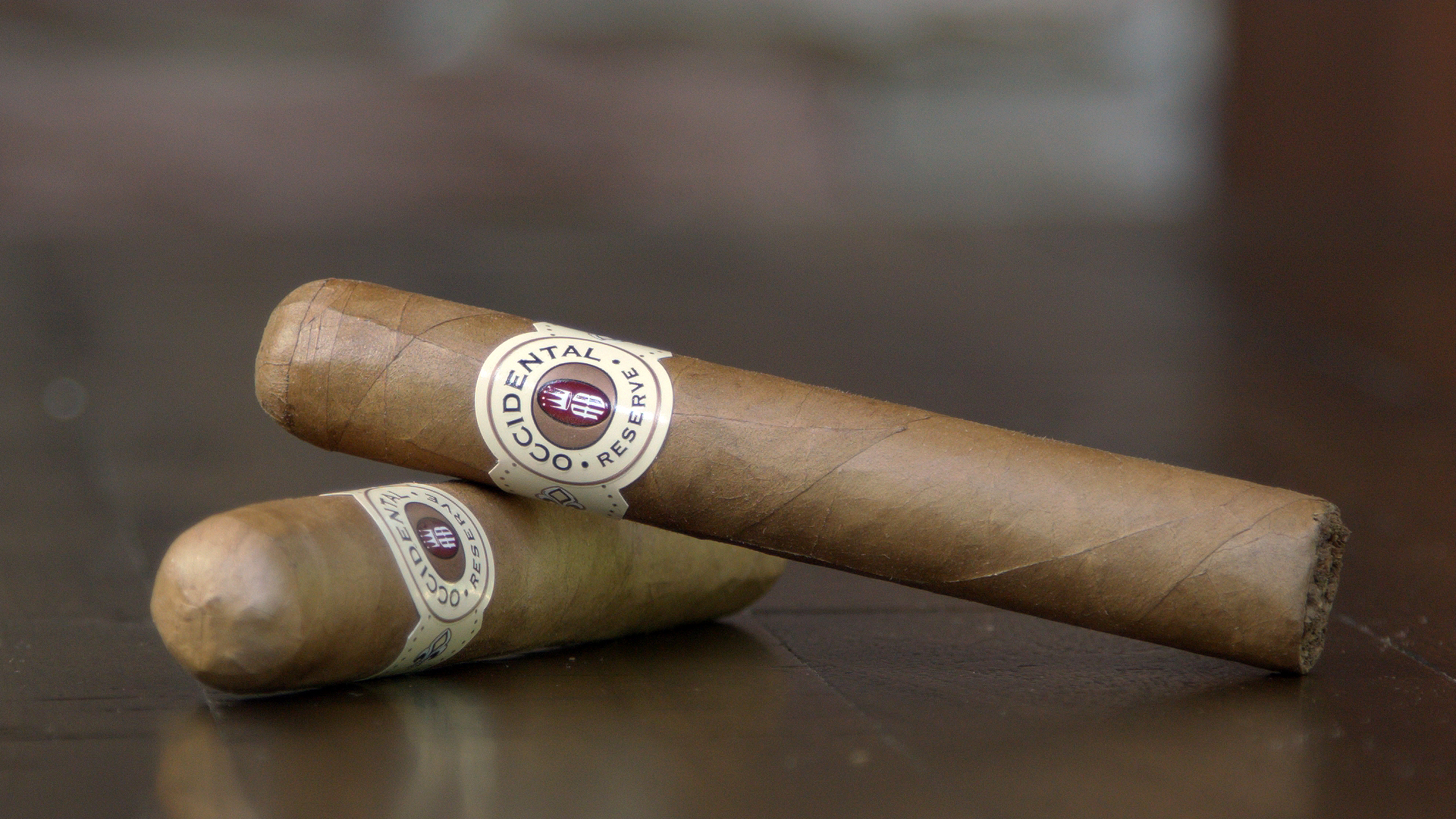 Two Alec Bradley Occidental Reserve Connecticut cigars sitting on a table outside of their cello